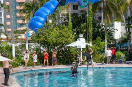 """Cyprien """"Woody"""" Rvx landing in the pool with a high five on Momo during one of his over 20 jumps during the event. - Team ILL Vision hosts the Acapulco BASE Boogie off the La Palapa hotel - Promoting tourism through Low Altitude Parachute Deployment Demonstration Jumping - Harry Parker Photography - Reflecting the best of your business, product, self."""
