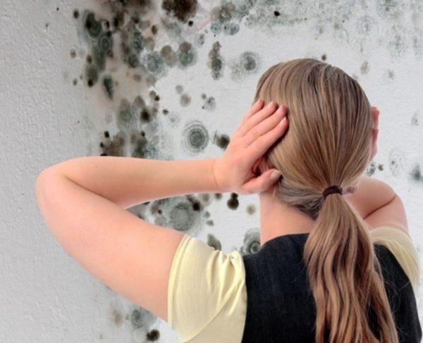 Femeia care ține capul la vederea unei ciuperci pe pereți