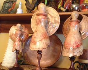 A collection of wooden angels and bowls crafted by Joe Ford.