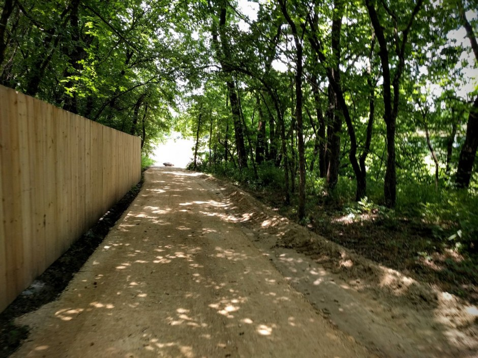 The trail runs alongside Elm Creek, next to a wooden fence that protects private property to the south.