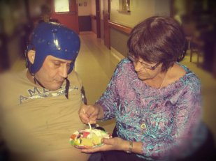 Barbara feeding Paul in the nursing home.
