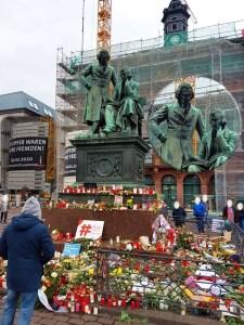 Blumen und Kerzen vor dem Brüder-Grimm-Denkmal