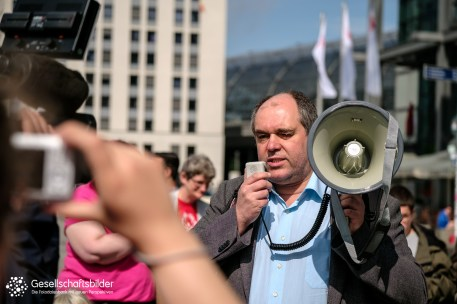 Ottmar Miles-Paul mit einem Megafon in der Hand, im Vordergrund eine Kamerafrau.