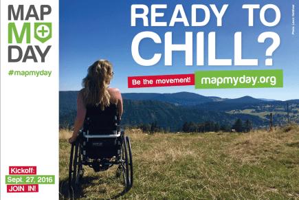 Eine blonde Frau im Rollstuhl sitzt auf einer Wiese und schaut in die Ferne. Dort sieht man Berge
