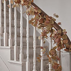 A leafy copper coloured garland on the handrail of an interior staircase