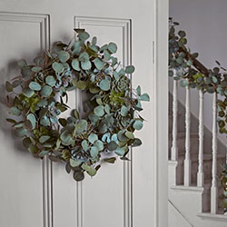 A wreath made of eucalyptus hanging on an interior grey painted door