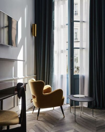 Chair next to window with long curtains