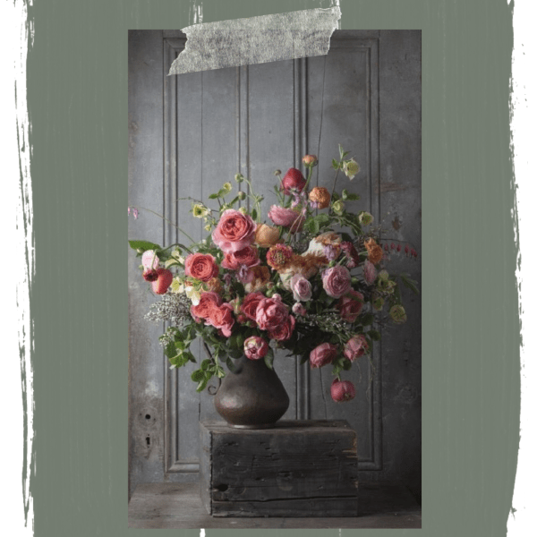 Pink roses in vase on old wooden crate