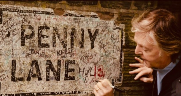 Paul McCartney autographs the Penny Lane sign in Liverpool.