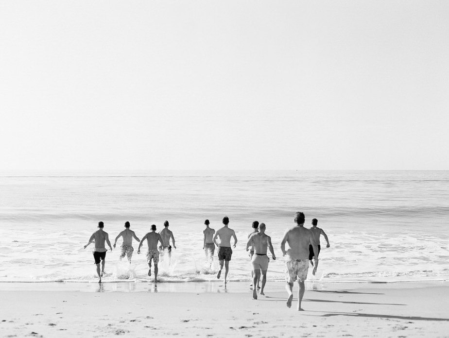 groomsmen running into the ocean