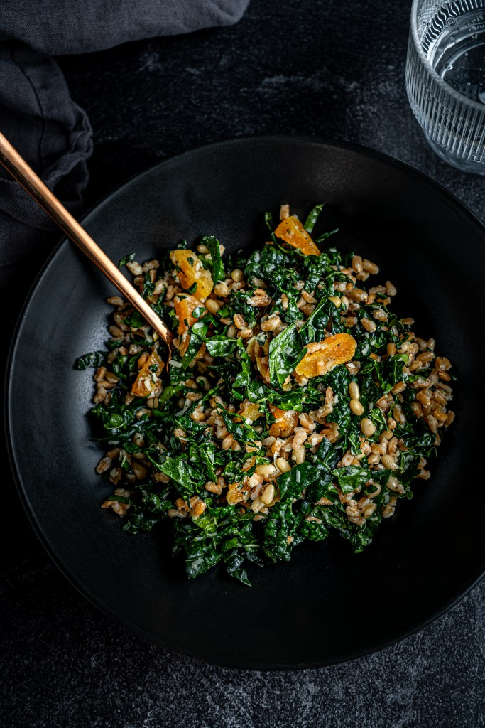 Vertical shot of chopped kale salad with apricots and farro.