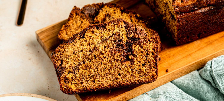 A close up header shot of a couple pieces of banana bread with a brigadeiro swirl.