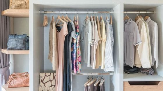 Clothes and bags in a small closet.