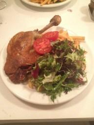 Un canard confit accompagné de sa salade et de frites (à l'origine, accompagné de pommes de terre)