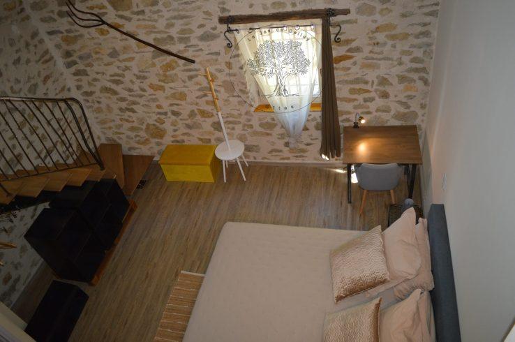 gîte de Belley chambre muscade de 17 m2 avec lit 160 cm et 4 oreillers et coussins déco avec bureau et escalier métallique rambarde donnant à l'espace détente à le jas de belley à montfort 04600 alpes de haute provence 04 escalier métallique et rambarde donnant à l'espace détente