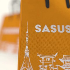 close up of our Sasushi PP non-woven cooler bag with black handles and a one colour logo print on an orange base.