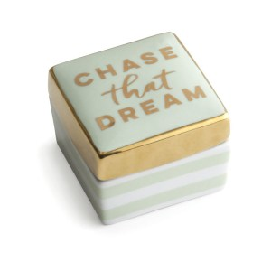 """A porcelain blue box, painted gold around the edge with the text """"Chase that dream"""" on the top"""