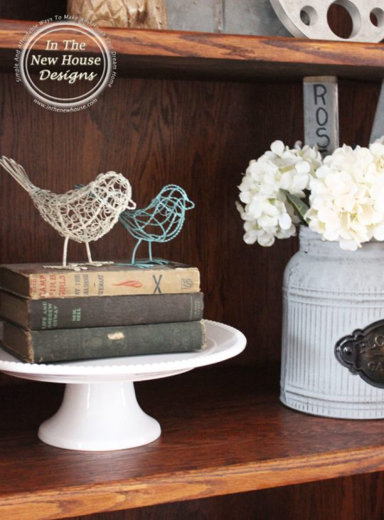Fill in space on open shelving and raise up collectibles with a cake stand