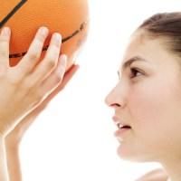 Woman shooting a ball into a basket