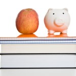 Books on prescription: apple and a piggy bank on top of books