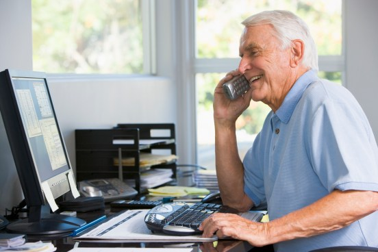 Man in home office on telephone using computer smiling