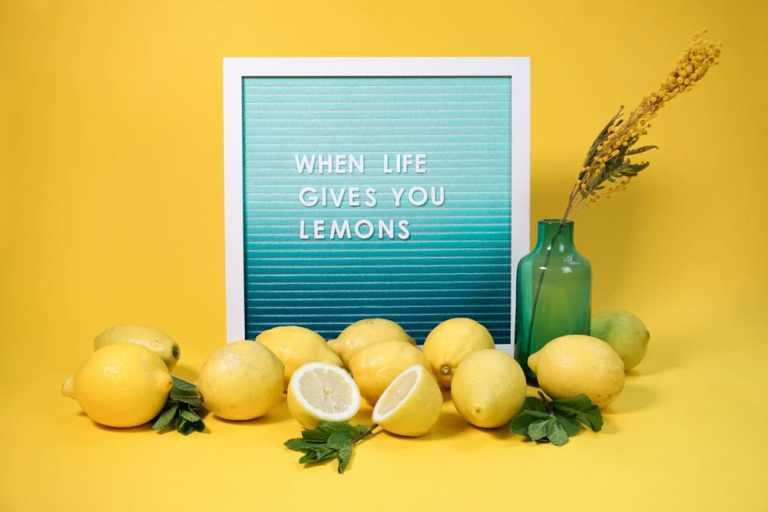 Buchstabentafel auf Filz vor gelbem Hintergrund mit Zitronen im Vordergrund