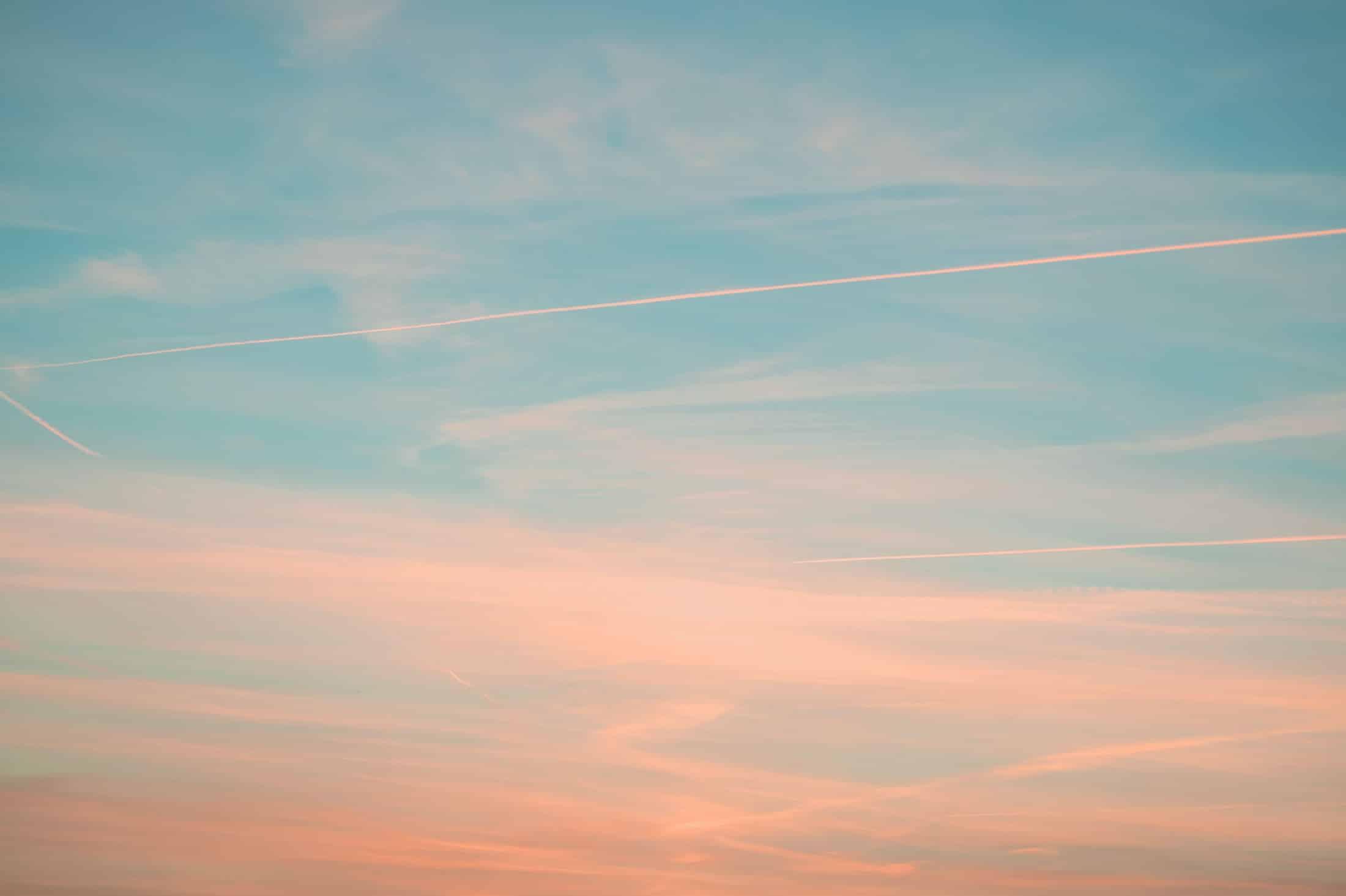 Himmel in Farben des Sonnenuntergangs mit Flugzeugstreifen