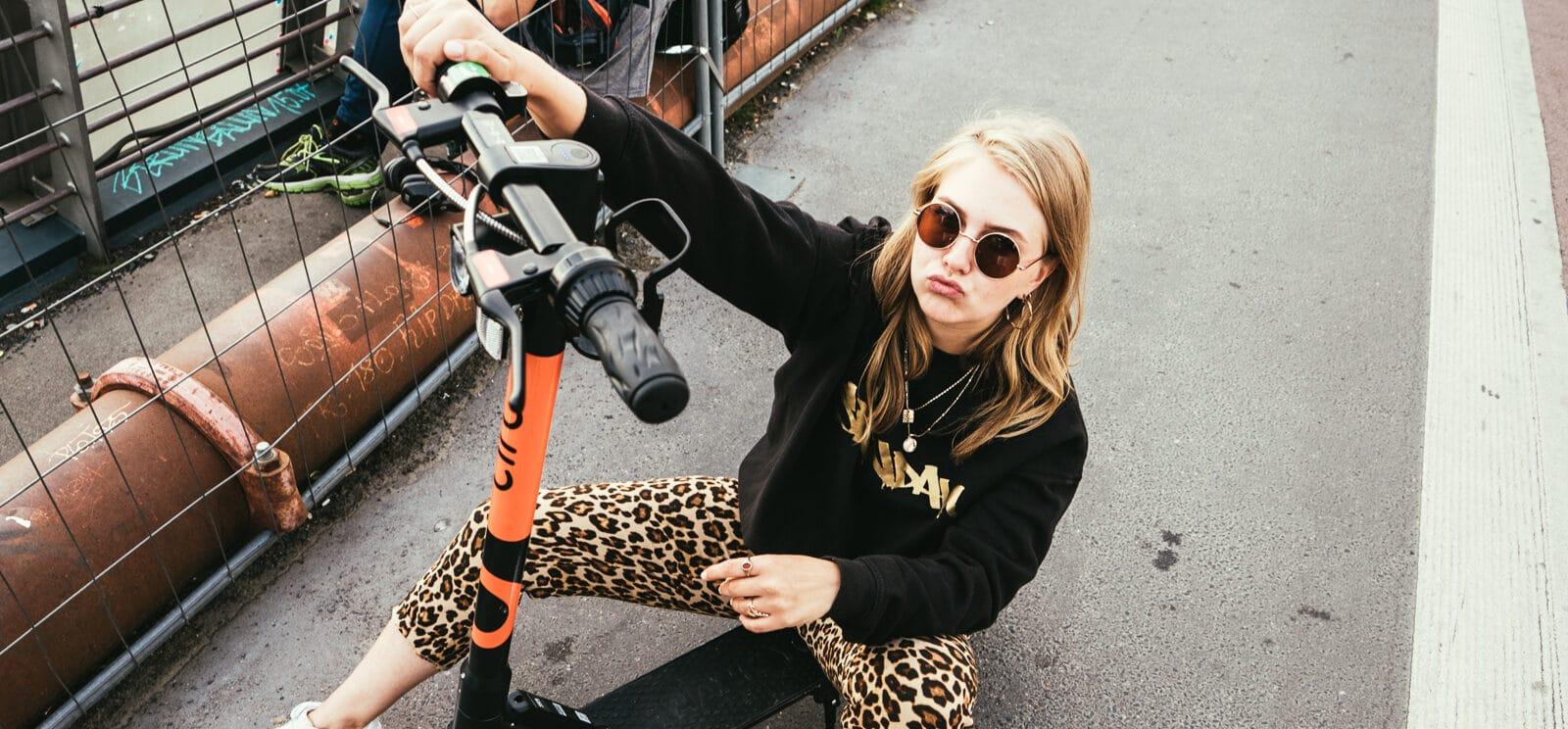 Foto von junger Frau die auf einem E-Roller sitzt und in die Kamera guckt. Aus dem Artikel: So ist mein Job als Social Media Managerin – 24/7 online?