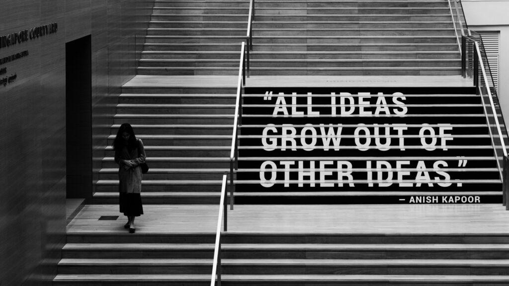 """Schwarz weiß Foto von einer Treppe auf der """"All ideas grow out of other ideas gemalt steht. Aus dem Artikel: So ist mein Job als Social Media Managerin – 24/7 online?"""