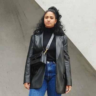 Junge Frau mit dunklen Locken steht vor einer grauen Wand. Sie trägt eine schwarze Lederjacke, ein schwarzes Oberteil, eine schwarze Tasche und eine blaue Momjeans. Aus dem Artikel: Wir fordern, dass der Frauentag 365 Tage im Jahr ist.