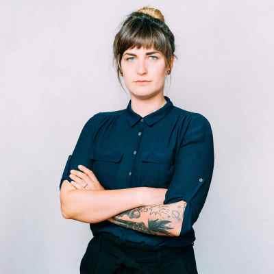 Junge Frau mit Dutt die ein navyfarbenen Hemd trägt und mit starkem Blick und verschränkten Armen in die Kamera guckt. Aus dem Artikel: Wir fordern, dass der Frauentag 365 Tage im Jahr ist.