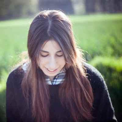Junge Frau mit braunen langen haaren, die nach unten schaut und lächelt. Sie trägt einen schwarzen Pullover und ein Karohemd daruntern. Aus dem Artikel: Wir fordern, dass der Frauentag 365 Tage im Jahr ist.