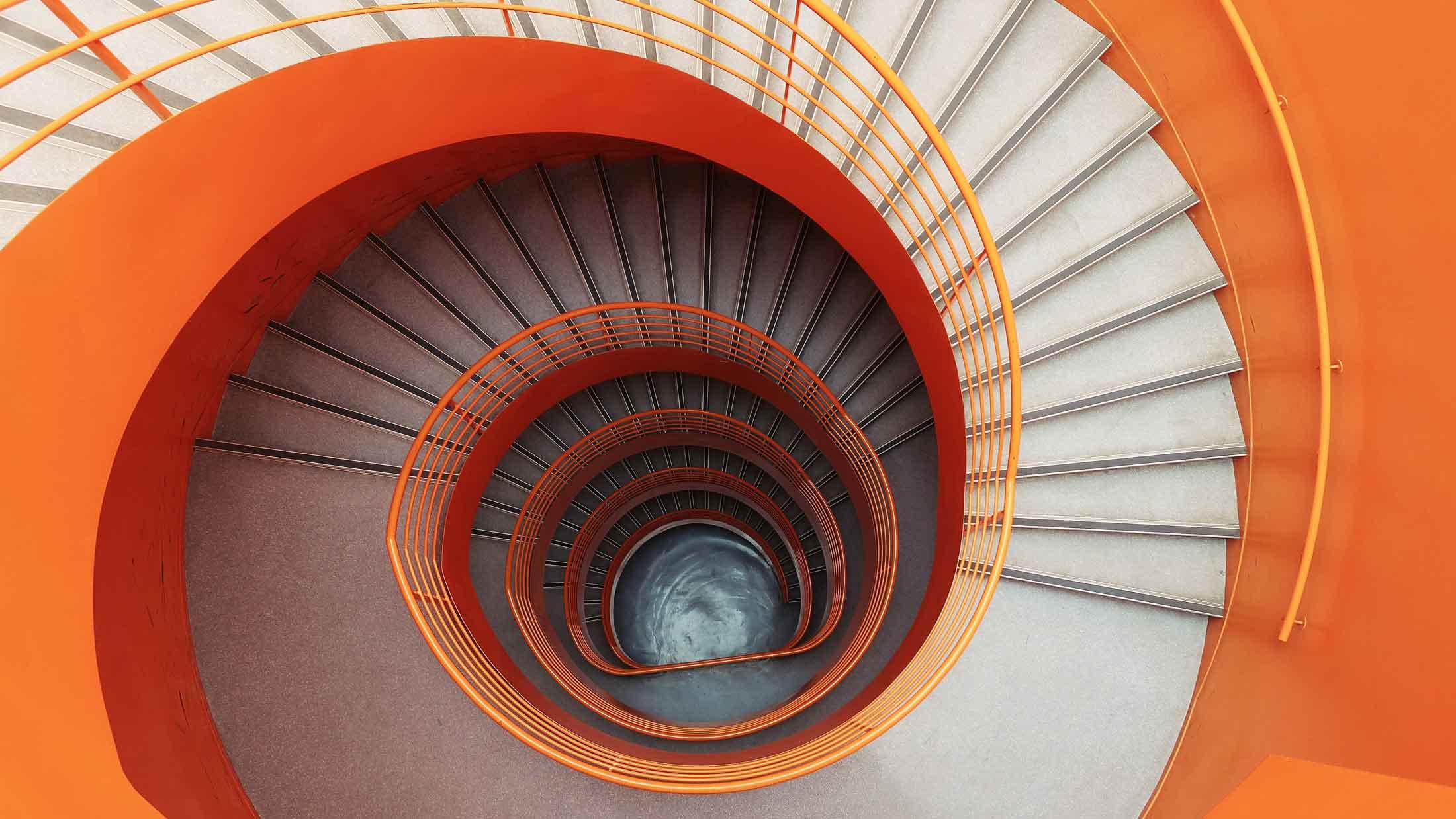 Bild einer organe farbenen Wendeltreppe. Von oben nach unten fotografiert. Aus dem Artikel Rückfall ist kein Rückschritt
