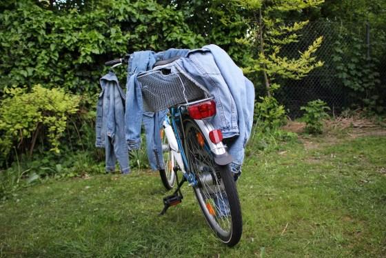 Fahrrad, an dem Jeansjacken aufgehängt sind