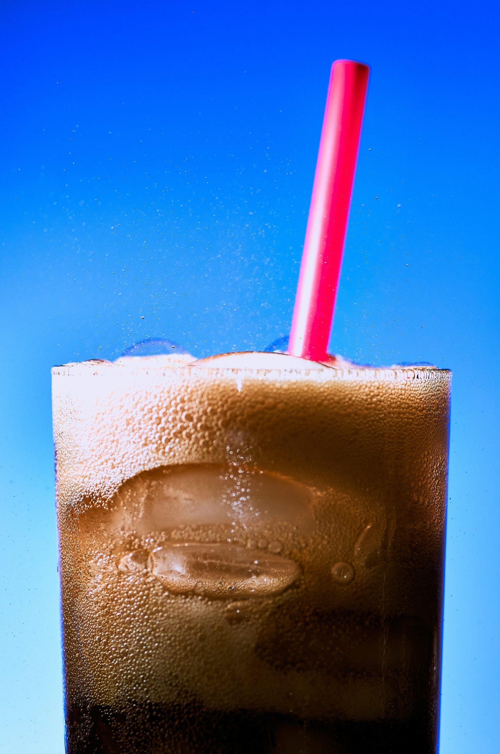 Glas voll kalter Cola mit Schaum und rotem Strohhalm, vor einem blauen Hintergrund.