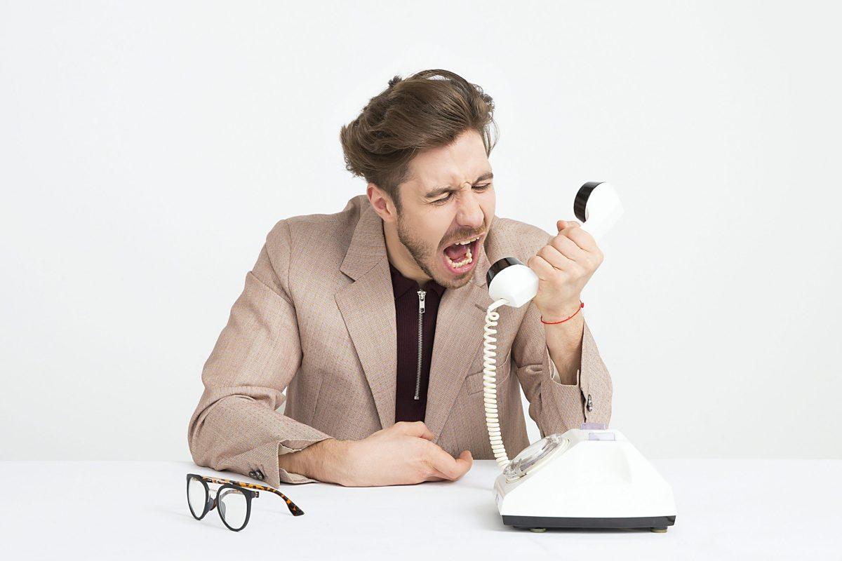 Mann im Anzug sitzt am Schreibtisch und schreit in ein Wahlscheibentelefon.