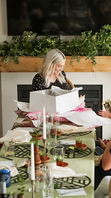 woman opening a gift at her baby shower