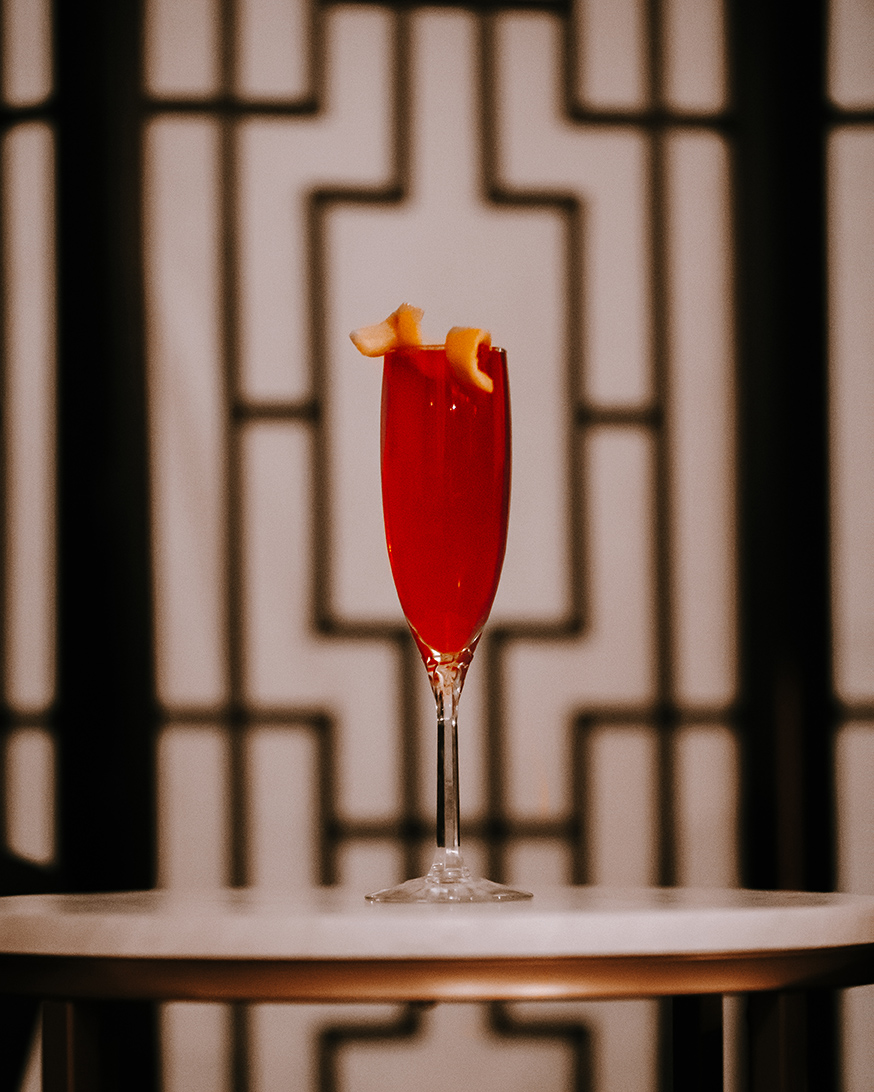 a cocktail in front of an art deco backdrop