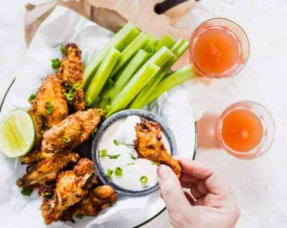 Extra Crispy Air Fryer Wings with celery and homemade ranch sauce on plate being picked up with hand. lenaskitchenblog.com