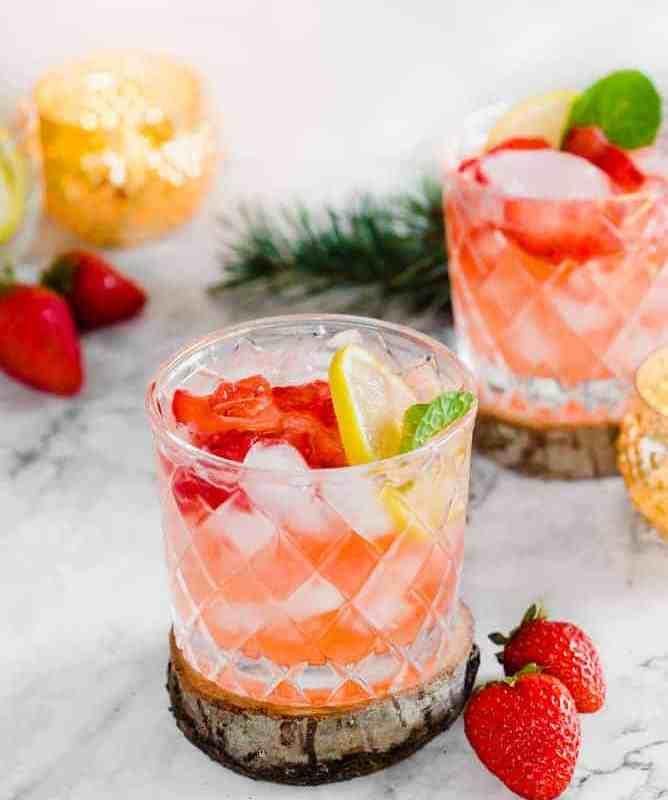 strawberry cocktail in glass with strawberries, lemons and mint