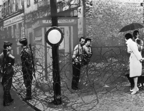 Một cặp Tây Đức và một cặp Đông Đức nói chuyện qua hàng rào kẽm gai dọc biên giới ở Berlin năm 1961. Bên trái là hai lính Đông Đức. (AP)