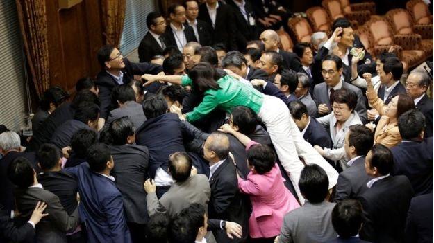 Các nghị sĩ bao vây chủ tịch ủy ban sau khi luật được thông qua. (Ảnh: AP)