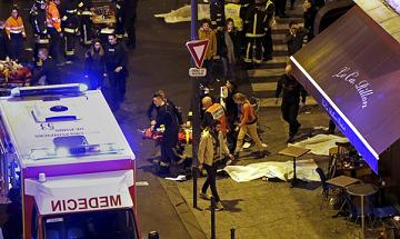 Lính cứu hỏa giúp một người bị thương gần rạp hát Bataclan hồi tháng 11-2015. (Ảnh: Christian Hartmann/Reuters)