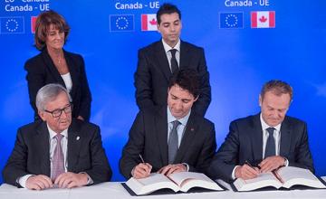 Thủ tướng Canada Justin Trudeau, ở giữa hàng trước, ký hiệp định CETA với Chủ tịch Ủy ban Châu Âu Jean-Claude Juncker, trái, và Chủ tịch Hội đồng Châu Âu Donald Tusk, phải, hôm 30-10 tại Brussels. (Ảnh: Thierry Monasse/Associated Press)