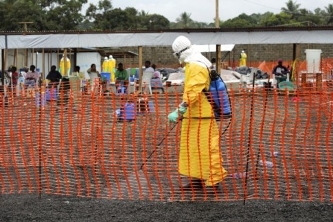 A hygienist disinfects the fence line at ELWA 3,  Photo: Caitlin Ryan/MSF