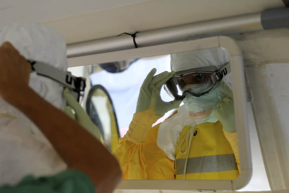 MSF OCB Board president, Meinie Nicolai checks her PPE in the mirror before going into the high risk zone at ELWA 3, MSF.s Ebola Management Centre in Monrovia. Photo: Caitlin Ryan/MSF