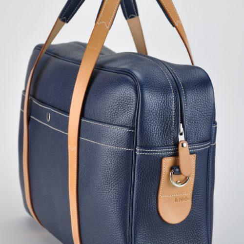 Sac bagage en cuir, intérieur doublé en tissu avec aménagement de poches. Poignées en vachette. Fabrication française de luxe.