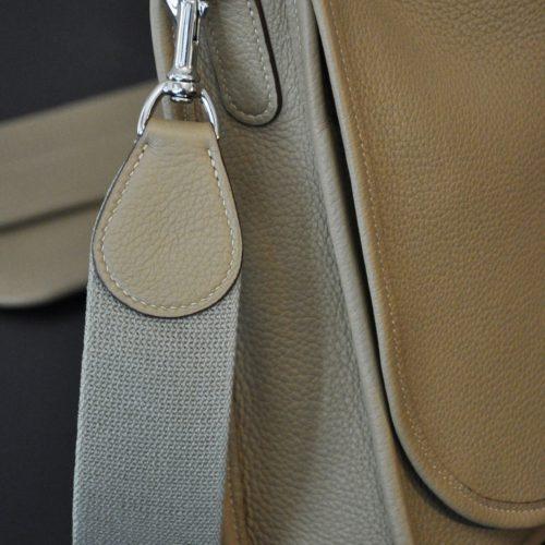 La besace est fabriquée avec une bandoulière large en toile, montée avec des mousquetons en laiton massif, finition nickelée. Fabrication française de luxe.