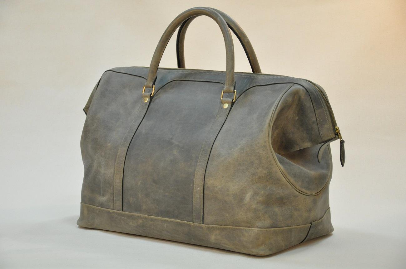 Ce bagage de luxe ravira les collectionneurs d'autos anciennes. Bagage qui a du style et du caractère, fabriqué en vachette couleur bronze vieilli, doublé en lin. LE NOËN créateur de maroquinerie de Luxe.