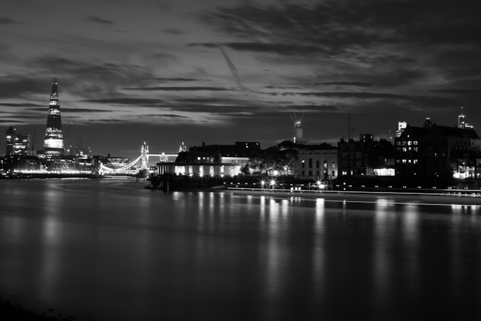 a monochrome image of the thames river - looking towards tower bridge and the shard